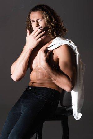 sexy shirtless man with long hair smoking on dark background