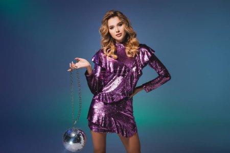 Photo pour Élégante femme en robe à paillettes avec boule disco sur fond bleu - image libre de droit