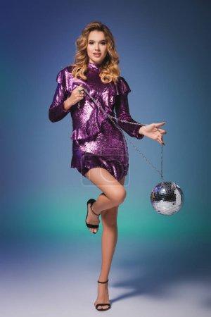 elegante Frau im Paillettenkleid mit Discokugel auf blauem Hintergrund