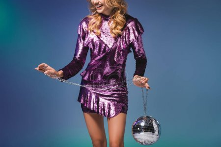 cropped view of happy elegant woman in sequin dress with disco ball on blue background