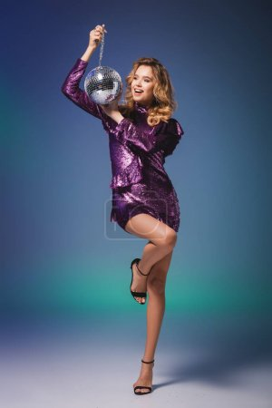 Photo for Happy elegant woman in sequin dress with disco ball on blue background - Royalty Free Image
