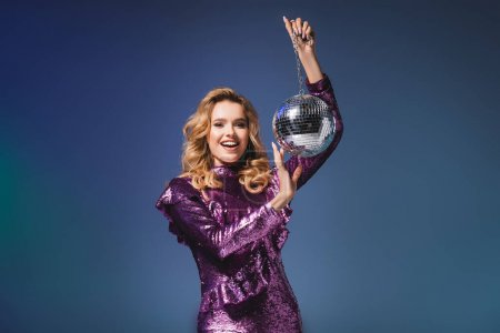 happy elegant woman in sequin dress with disco ball on blue background