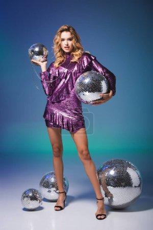 elegante Frau im Paillettenkleid posiert mit Discokugeln auf blauem Hintergrund