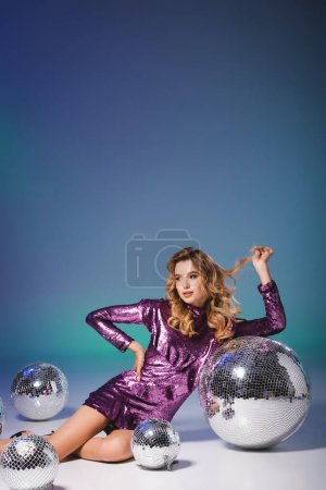 elegant woman in sequin dress posing on floor with disco balls