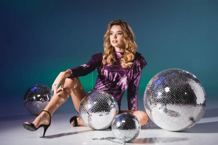 Photo for Elegant woman in sequin dress posing on floor with disco balls - Royalty Free Image