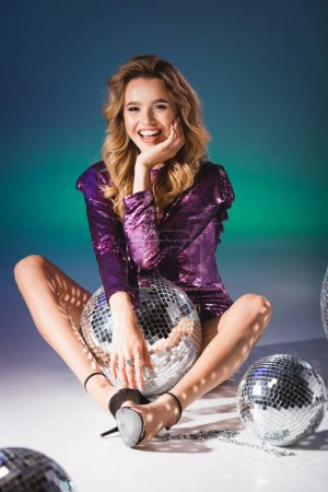 Photo for Happy elegant woman in sequin dress posing on floor with disco balls - Royalty Free Image