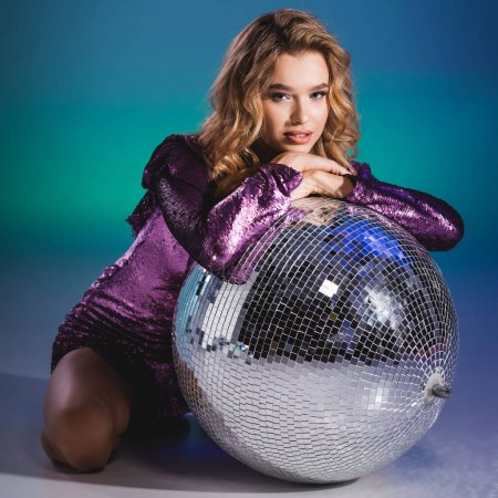 Photo for Elegant woman in sequin dress posing on floor with disco ball - Royalty Free Image