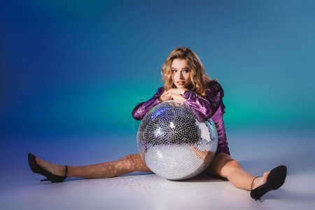 elegant woman in sequin dress posing on floor with disco ball