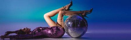 élégante femme en robe à paillettes couchée sur le sol avec boule disco, bannière