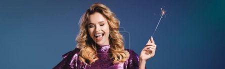 Photo for Happy elegant woman in sequin dress with sparkler on blue background, banner - Royalty Free Image
