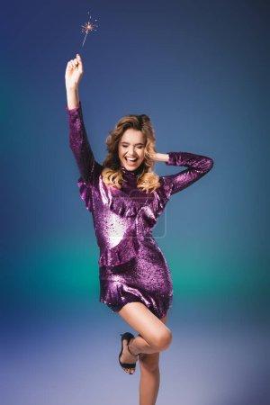 Photo pour Heureuse femme élégante en robe de paillettes avec étincelant sur fond bleu - image libre de droit
