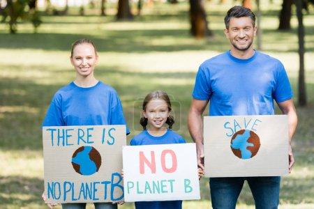 Lächelnde Familie von Aktivisten mit Plakaten, auf denen keine Inschrift des Planeten B zu sehen ist, Umweltkonzept