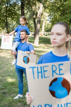 niña sentada en el hombro de los padres, y madre de pie en primer plano borrosa mientras sostiene pancartas con no hay inscripción planeta b, concepto de ecología