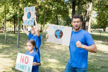 famille de bénévoles tenant des pancartes avec globe et il n'y a pas de planète b inscription, concept d'écologie