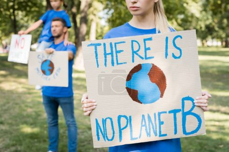 Photo for Woman holding placard with globe and there is no planet b inscription near family with posters on blurred background, ecology concept - Royalty Free Image