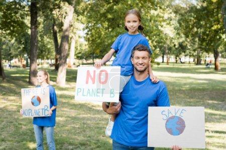 familia feliz de voluntarios sosteniendo pancartas con no hay planeta b inscripción y globo, concepto de ecología