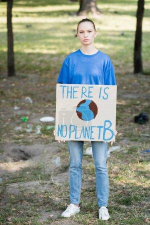 mujer mirando a la cámara mientras sostiene la pancarta con globo y no hay inscripción planeta b