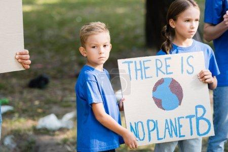 enfants tenant une pancarte avec globe et il n'y a pas d'inscription planète b près des parents, concept d'écologie