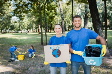 couple holding placard with globe, save inscription, and rubbish container, while children collecting waste on blurred background, ecology concept