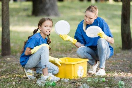 Foto de Hija y madre recogiendo basura plástica en contenedor con símbolo de reciclaje, concepto de ecología - Imagen libre de derechos