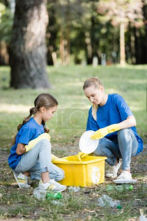 Photo for Mother with daughter collecting plastic garbage in container with recycling symbol, ecology concept - Royalty Free Image