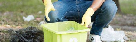 Photo pour Vue recadrée de bénévoles ramassant des déchets en plastique dans un conteneur, une bannière - image libre de droit