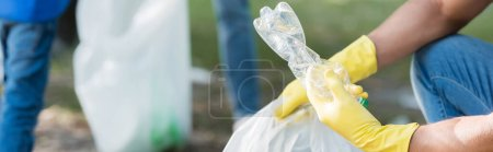 cropped view of man in rubber gloves holding plastic bottle near family on blurred background, ecology concept, banner