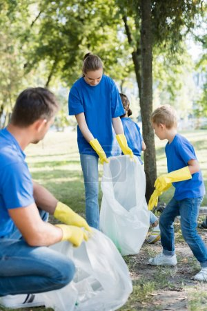 family of activists collecting waste in recycled plastic bags, ecology concept