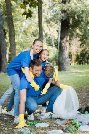 Photo for Happy family embracing father while collecting plastic rubbish in forest, ecology concept - Royalty Free Image