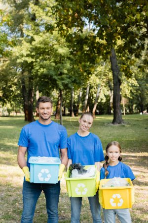 Photo for Smiling volunteers family holding containers with recycling emblems, full of plastic rubbish, ecology concept - Royalty Free Image