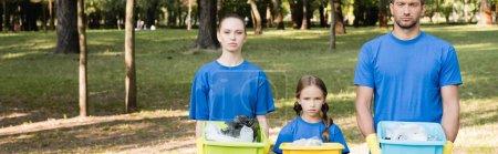 Photo pour Famille de bénévoles tenant des conteneurs remplis de déchets plastiques, concept écologique, bannière - image libre de droit