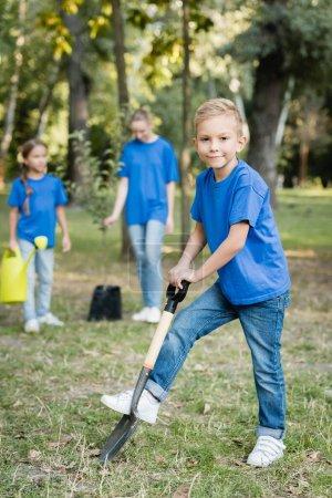 Photo pour Garçon creuser terrain avec pelle près de mère et soeur avec arrosoir et jeune semis sur fond flou, concept d'écologie - image libre de droit