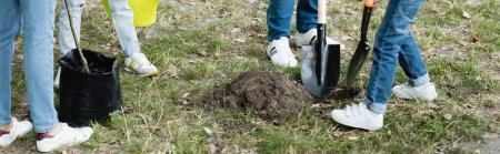 Photo pour Vue recadrée du père et du fils creusant un terrain près de la mère et de la fille avec un jeune arbre, concept écologique, bannière - image libre de droit
