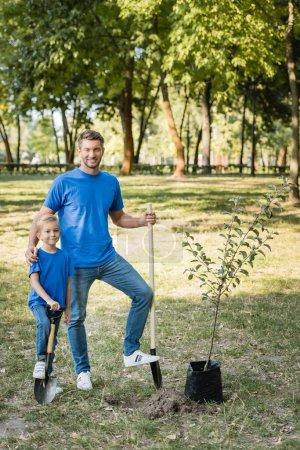 Photo pour Père et fils debout près du jeune arbre avec des pelles, concept d'écologie - image libre de droit
