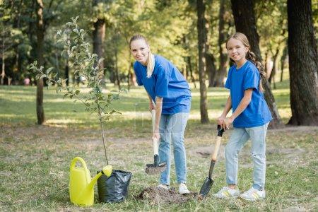 Foto de Madre e hija sonriendo a la cámara mientras cavan terreno cerca de un árbol joven y una regadera, concepto de ecología - Imagen libre de derechos