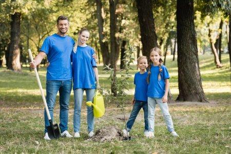Photo pour Heureux famille de bénévoles debout près planté jeune arbre avec pelle et arrosoir, concept d'écologie - image libre de droit