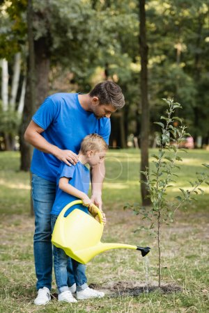 Photo for Father and son watering young tree planted in park, ecology concept - Royalty Free Image