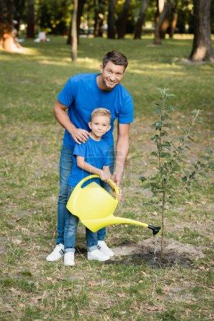 garçon regardant caméra tout en arrosant planté jeune arbre près du père souriant, concept d'écologie