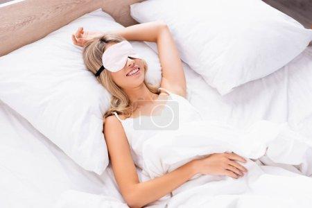 Photo pour Femme souriante dans le bandeau couché sur la literie blanche le matin - image libre de droit