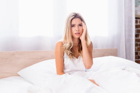 Confused woman in pajamas looking at camera while sitting on bed