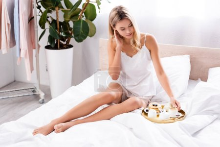 Photo pour Jeune femme tenant une tasse de café près des crêpes et des fleurs d'oeillet sur le plateau de petit déjeuner au lit - image libre de droit