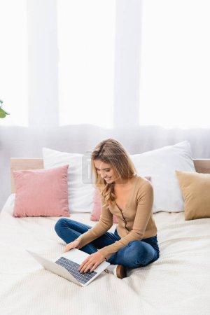 Femme souriante travaillant sur un ordinateur portable tout en étant assis sur le lit à la maison