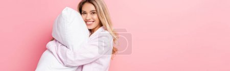 Photo for Woman in pajamas holding white pillow and smiling at camera on pink background, banner - Royalty Free Image