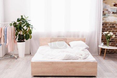 Photo pour Chambre avec plantes, réveil et porte-cintre avec vêtements - image libre de droit
