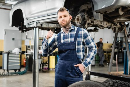 Photo for Young mechanic showing thumb up while holding hand in pocket near raised car - Royalty Free Image