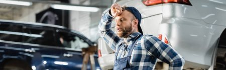 young tired repairman holding hand near forehead in workshop, banner