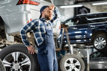 tired technician holding hand near forehead while leaning on car wheel on blurred background