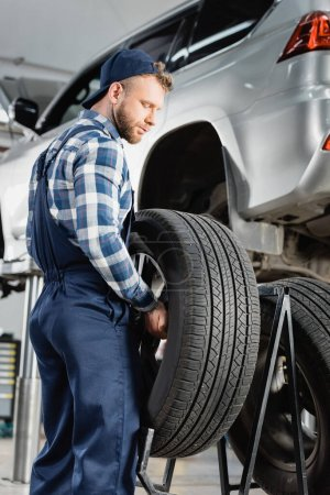 mechanic in overalls holding wheel near automobile raised on car lift on blurred background