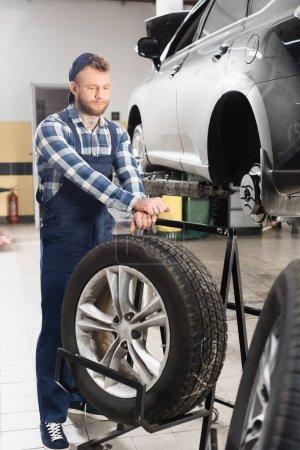 Photo pour Technicien en vêtements de travail près de la roue et de l'automobile soulevé sur l'ascenseur de voiture au premier plan flou - image libre de droit