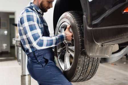 Photo for Cropped view of young technician fixing wheel on car in workshop - Royalty Free Image